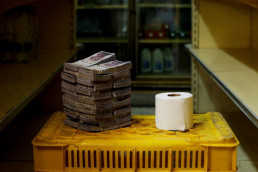 Toilet paper roll next to a pile of bills